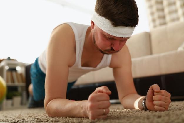 Der typ macht die plankenübung auf dem teppich in der wohnung abnehmen mit fitness