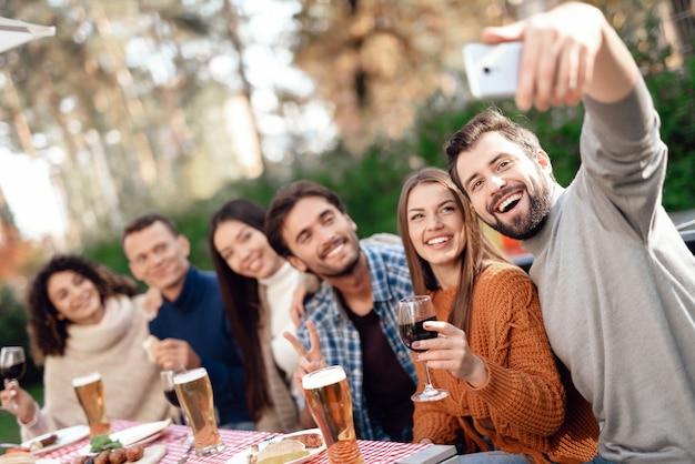 Der typ macht ein selfie mit freunden auf dem smartphone.