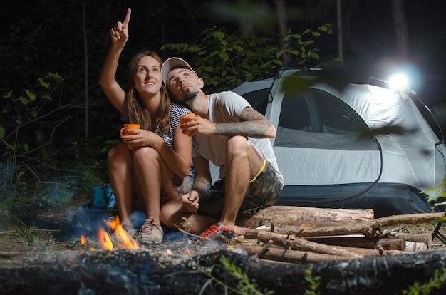 Der typ mit dem mädchen im wald mit einem zelt in der nacht, am lagerfeuer sitzend