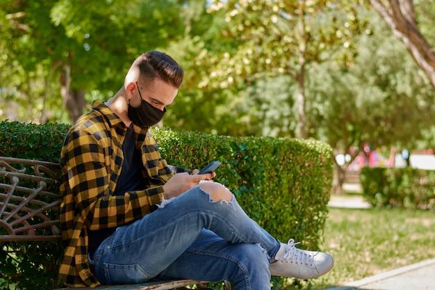 Der typ mit der maske sitzt auf einer bank, während er mit seinem handy schreibt