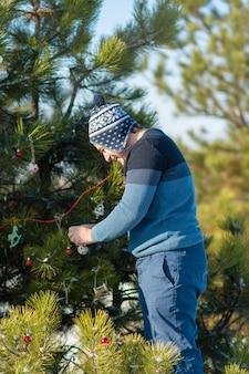 Der typ schmückt mit einem dekorativen spielzeug und einer girlande einen grünen weihnachtsbaum auf der straße im winter im wald. christbaumschmuck.