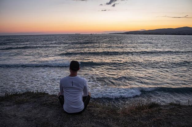 Der typ sitzt am rand einer klippe und schaut auf die wunderschöne seelandschaft und die wellen. ruhe und meditation nach einem langen training.