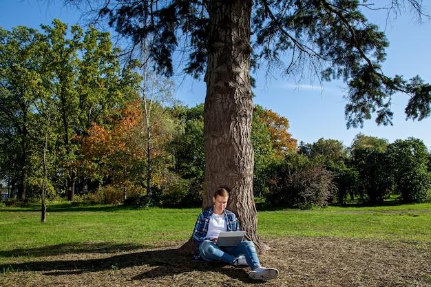 Der typ sitzt neben einem baum im park und arbeitet an einem laptop. freiberufliche tätigkeit im freien. arbeiten außerhalb des büros aufgrund der covid-19-pandemie