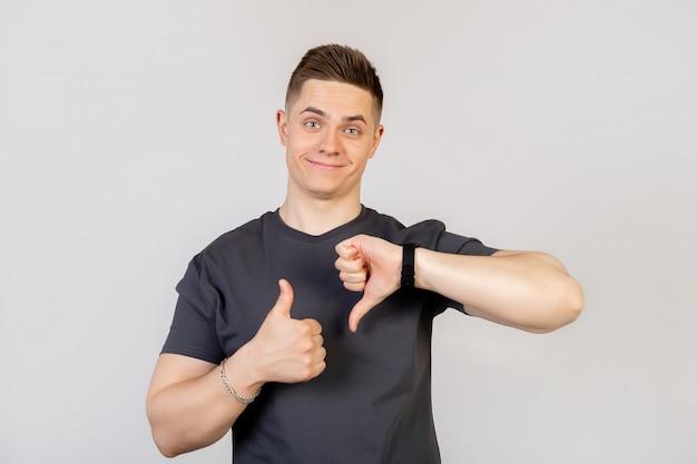 Der typ zeigt eine geste mit dem finger auf und ab. junger hübscher mann