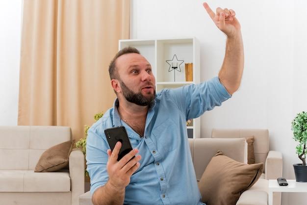 Der überraschte erwachsene slawische mann sitzt auf einem sessel, hält das telefon und zeigt nach oben in das wohnzimmer