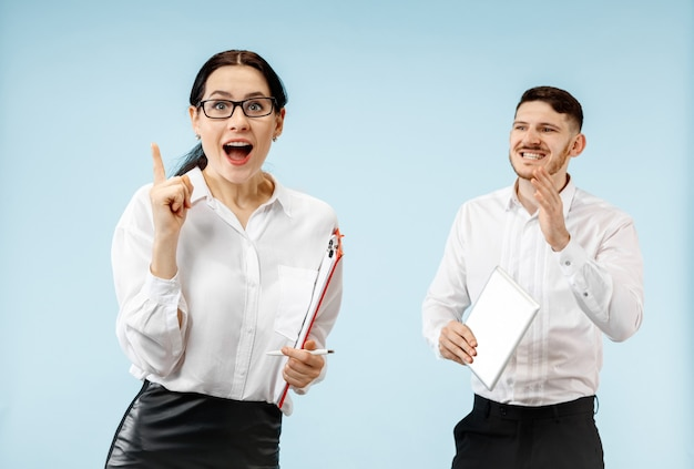 Der überraschte geschäftsmann und die überraschte frau, die auf einem blauen studiohintergrund lächeln