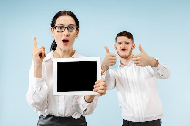 Der überraschte geschäftsmann und die überraschte geschäftsfrau, die auf einem blauen studiohintergrund lächeln und leeren bildschirm des laptops oder des tablets zeigen