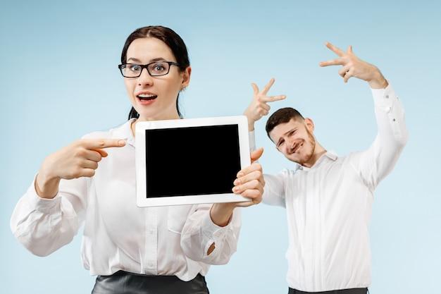 Der überraschte geschäftsmann und die überraschte geschäftsfrau lächeln auf einer blauen wand und zeigen leeren bildschirm des laptops oder des tablets