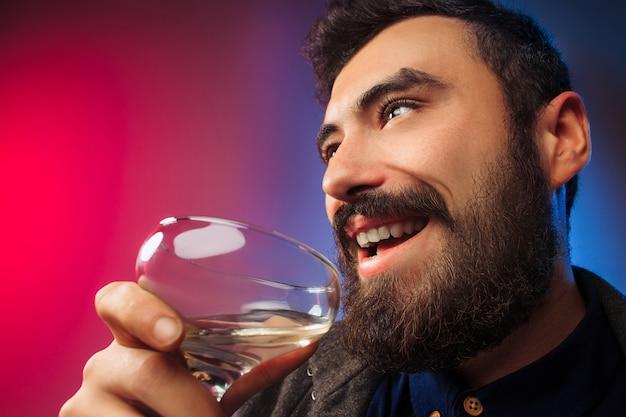 Der überraschte junge mann posiert mit einem glas wein.