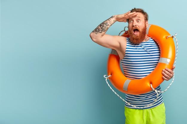 Der überraschte junge urlauber mit roten haaren und bart kommt mit sicherheitsausrüstung an den strand, da er nicht schwimmen kann