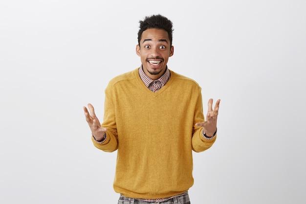 Der überraschte mann kann nicht glauben, dass ihm glück gekommen ist. aufgeregter glücklicher afroamerikanischer mitarbeiter, der palmen schüttelt und breit lächelt, während er freund über graue wand aufregende positive nachrichten erzählt
