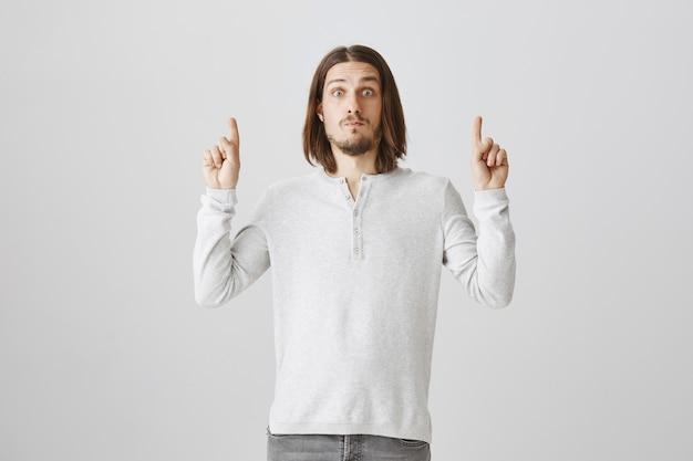 Der überraschte mann starrte schockiert, als er mit den fingern nach oben zeigte