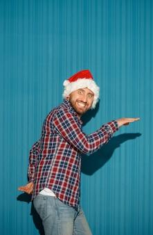 Der überraschte weihnachtsmann, der eine weihnachtsmütze auf dem blauen hintergrund trägt