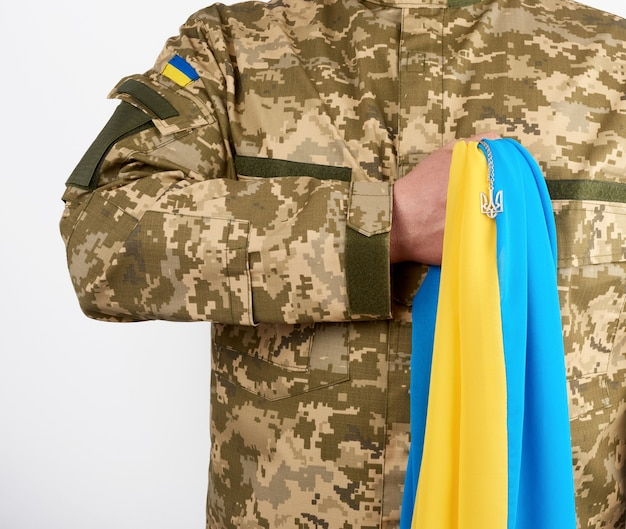 Der ukrainische krieger in einer militärischen pixeluniform hält die gelb-blaue flagge des ukrainischen staates und an der kette ein kleines wappen des dreizacklandes