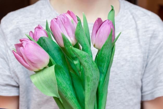 Der unerkennbare junge, der ein bouquete des frühlinges hält, blüht rosa tulpen