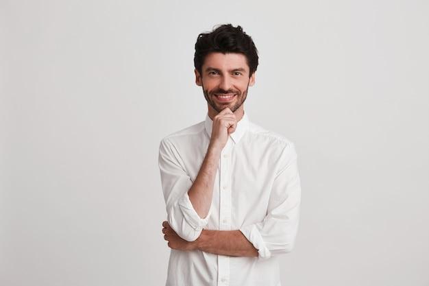 Der unrasierte, selbstbewusste, stilvolle mann denkt über sein neues leben nach, hält seine hand unter dem kinn, trägt ein weißes freizeithemd und lächelt.