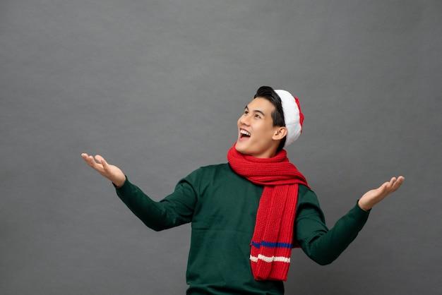 Der unterhaltene asiatische mann, der weihnachtsmotiv trägt, kleidet mit offener palmengeste
