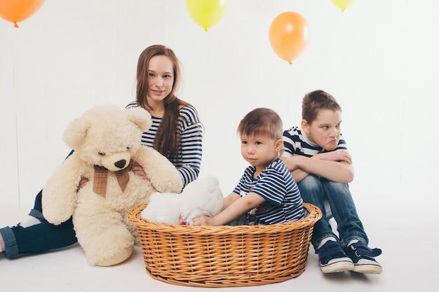 Der urlaub, lustige familie auf der party. kinder in einem korb mit einem großen teddybären auf einem weißen hintergrund unter den farbigen kugeln feiern ihren geburtstag