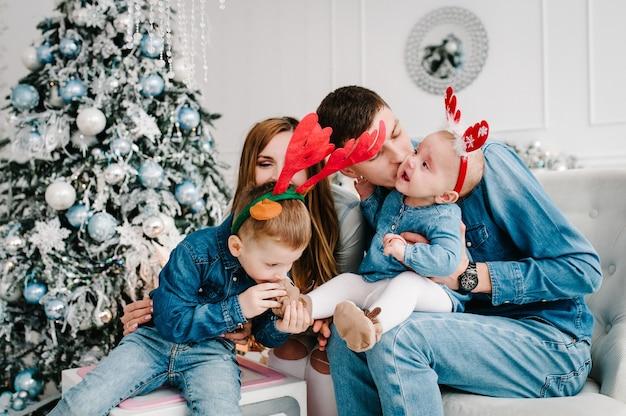 Der vater, die mutter hält einen kleinen sohn und eine kleine tochter in der nähe des weihnachtsbaums