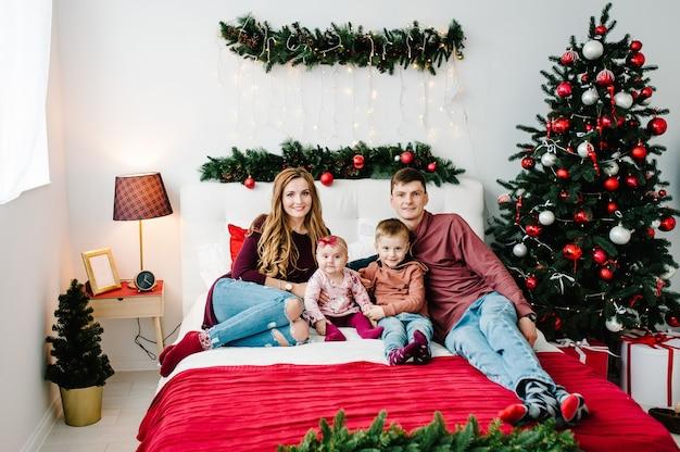Der vater, die mutter umarmen sohn und tochter auf dem bett nahe weihnachtsbaum. fröhliche weihnachten.