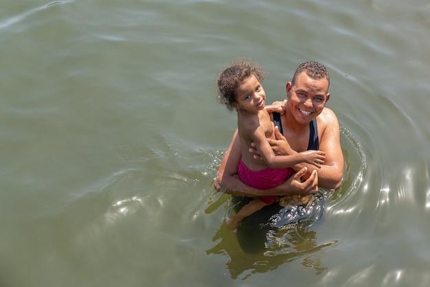 Der vater eines jungen mannes im wasser hält ihre tochter