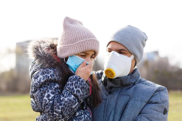 Der vater trägt seiner kleinen tochter eine maske, um das kind vor luftverschmutzung und covid-19 zu schützen, konzept des lebensstils der menschen in der krise des krankheitsausbruchs und des luftproblems.