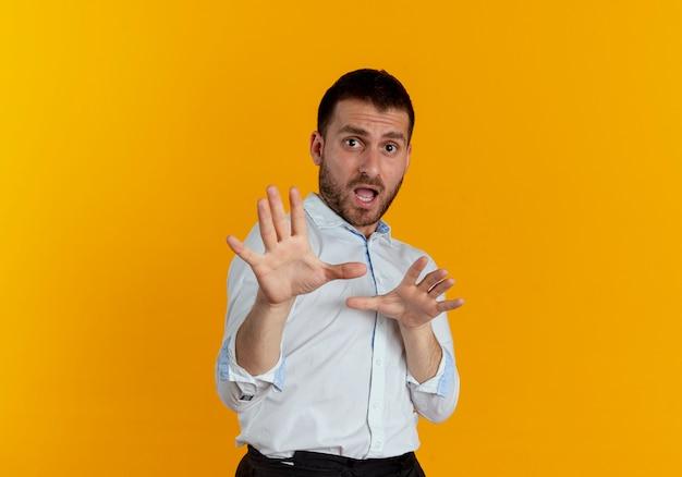 Der verängstigte gutaussehende mann gibt vor, mit auf orangefarbener wand isolierten händen zu verteidigen