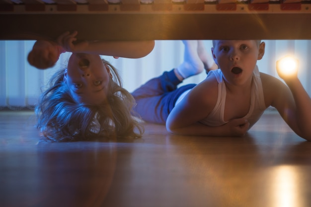 Der verängstigte junge und das verängstigte mädchen mit einer taschenlampe schauen unter das bett. nachtzeit