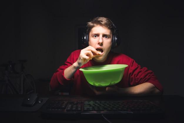 Der verängstigte kerl sieht sich zu hause am computer horrorfilme an
