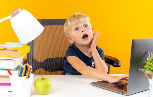 Der verängstigte kleine schuljunge, der mit schulwerkzeugen am tisch sitzt, benutzte einen laptop, der die hand auf die wange legte