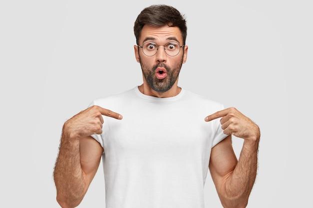 Der verblüffte junge mann zeigt auf die leerstelle des t-shirts