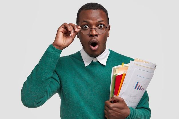Der verblüffte männliche finanzier ist schockiert, den buchhaltungsbericht zu überprüfen, die einnahmen aus dem startup zu analysieren, die hand am rand der brille zu halten und den mund vor überraschung zu öffnen