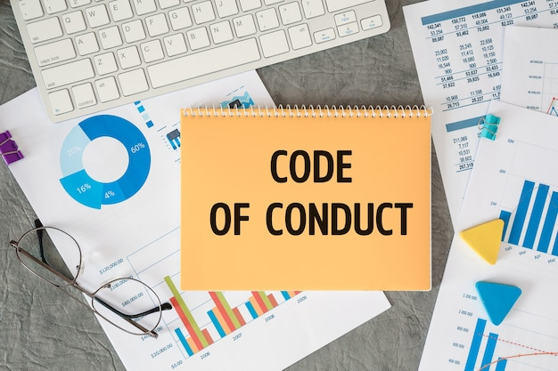 Der verhaltenskodex ist in einem dokument mit bürozubehör auf dem schreibtisch vermerkt.