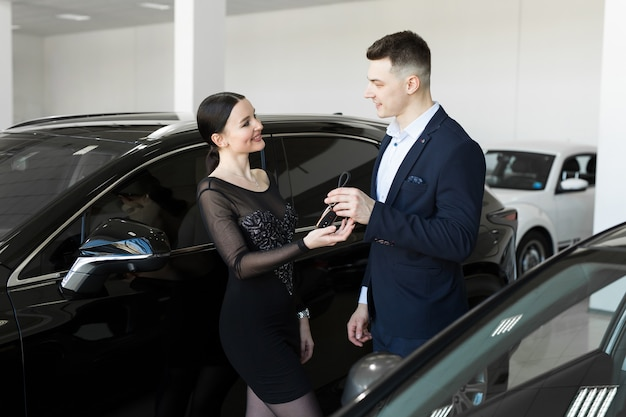 Der verkäufer gibt dem käufer die schlüssel für ein neues auto im ausstellungsraum