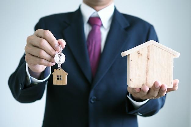 Der verkäufer hält den hausschlüssel. bereiten sie den versand an den neuen hausbesitzer vor.