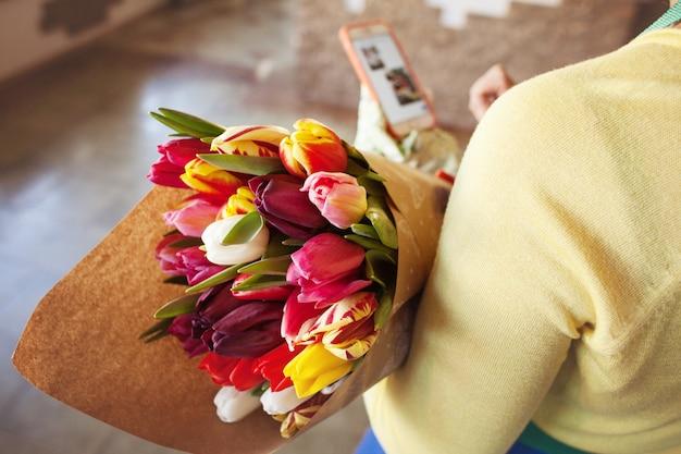 Der verkäufer hält einen großen schönen strauß tulpen in kraftpapier verpackt. ansicht von oben