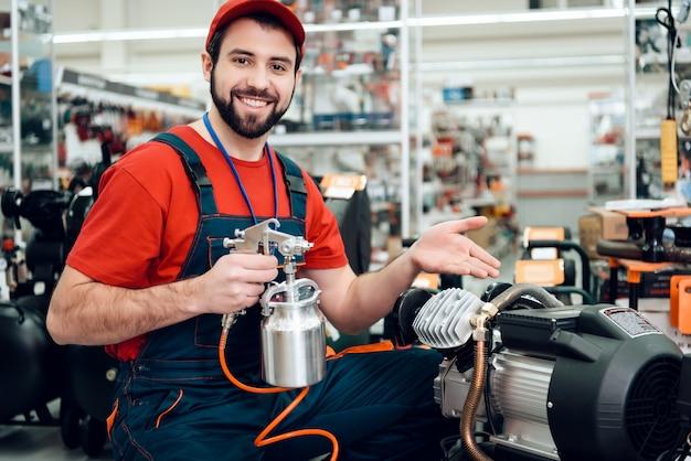 Der verkäufer präsentiert ein neues kompressor-farbspritzgerät