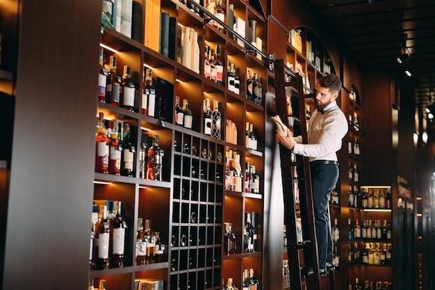 Der verkäufer von alkoholischen getränken sortiert flaschen, die auf der leiter stehen