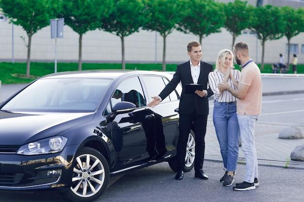 Der verkäufer zeigt den käufern ein neues auto. junger mann und junge frau wählen ein auto im freien. testen sie ein neues auto.