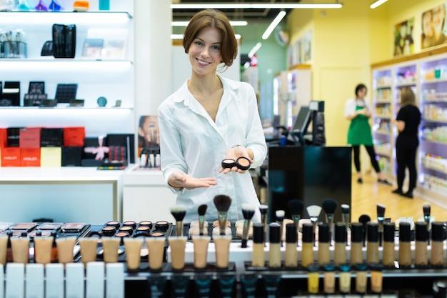 Der verkaufsassistent im make-up-store hilft bei der auswahl des fundaments