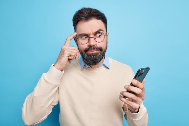 Der verlegene bärtige mann, der sich auf das smartphone konzentriert, hält den finger auf den tempel und versucht, sich auf die informationen zu konzentrieren, die in ordentlichen pullover-posen gegen die blaue wand gekleidet sind. technologiekonzept
