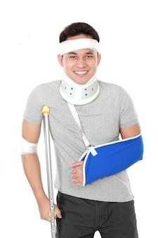 Der verletzte junge mann trägt eine armschlaufe und eine krücke