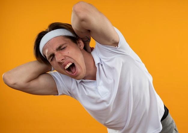 Der verletzte junge sportliche mann, der stirnband und armband trägt, packte den schmerzenden hals, der auf der orangefarbenen wand isoliert wurde