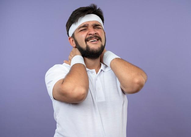 Der verletzte junge sportliche mann, der stirnband und armband trug, packte den schmerzenden nacken