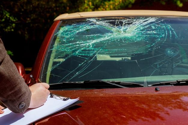 Der versicherungsvertreter schätzt die kosten eines beschädigten autos nach einem zusammenstoß mit einem hirsch
