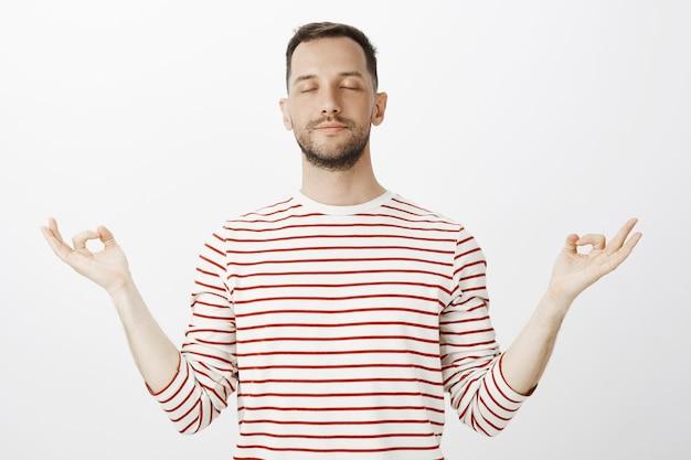 Der versuch, frieden im körper zu finden. porträt eines ruhigen, entspannten, gutaussehenden mannes, der die augen schließt und die hände mit einer zen-geste beiseite spreizt