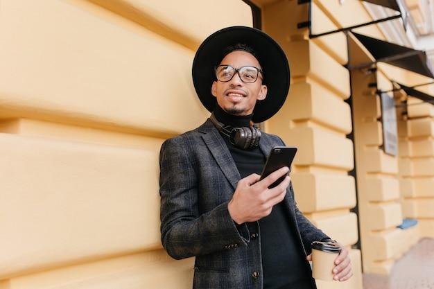 Der verträumte junge mann trägt einen stilvollen schwarzen anzug, der wegschaut, während er mit einer tasse tee auf der straße steht. beschäftigter afrikanischer kerl, der jemanden wartet und smartphone und kaffee hält.