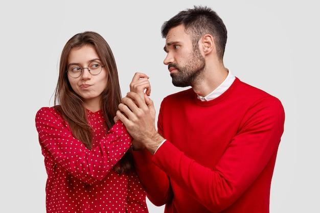 Der verzweifelte junge kaukasische mann hält die hand einer freundin, schaut mit miserablem gesichtsausdruck, bittet um vergebung, fühlt sich schuldig. paar haben uneinigkeit