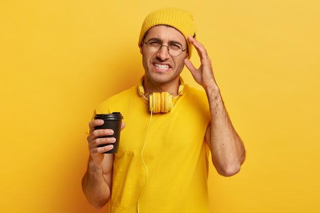 Der verzweifelte junge mann hat kopfschmerzen, fühlt sich überarbeitet und berührt die schläfe, beißt die zähne zusammen, trägt gelbe, lebendige kleidung, hält eine kaffeetasse zum mitnehmen und trägt eine runde brille. negatives gefühlskonzept