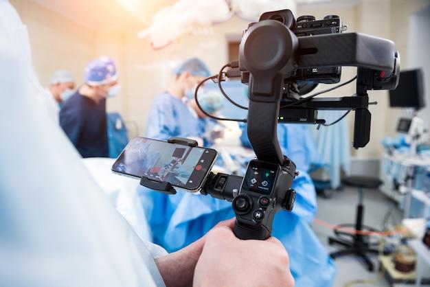Der videofilmer erschießt den chirurgen und die assistenten im operationssaal mit chirurgischer ausrüstung